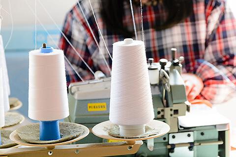 腕章のデザインを専用生地に印刷した後に1つ1つ腕章へ縫い上げていきます。ホツレが出ないように側面を丁寧に三つ巻きで縫っていきます。
