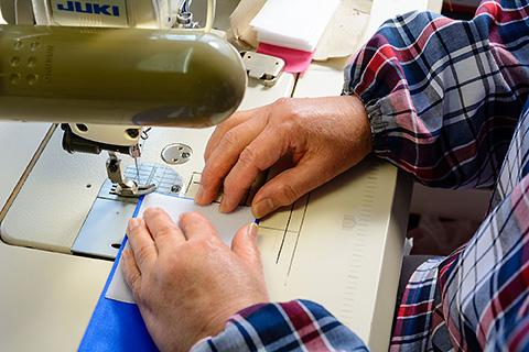 専用生地は通常の布に比べて硬く、生地自体にも微妙な幅の違いがある中で、できるだけ9cm幅に仕上がるように縫っていきます。職人さんの熟練の技術によって可能になります。
